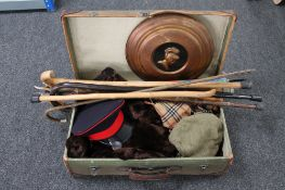 A vintage suitcase containing various clothing, walking sticks,