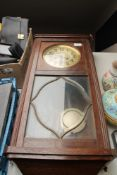 An early 20th century oak cased wall clock with silvered dial pendulum and key