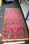 A Persian rug on raspberry ground,