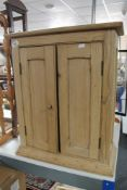 A pine double door cabinet CONDITION REPORT: This is a wall cabinet.