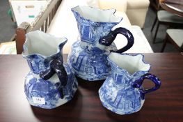 A set of three graduated blue and white Staffordshire style jugs