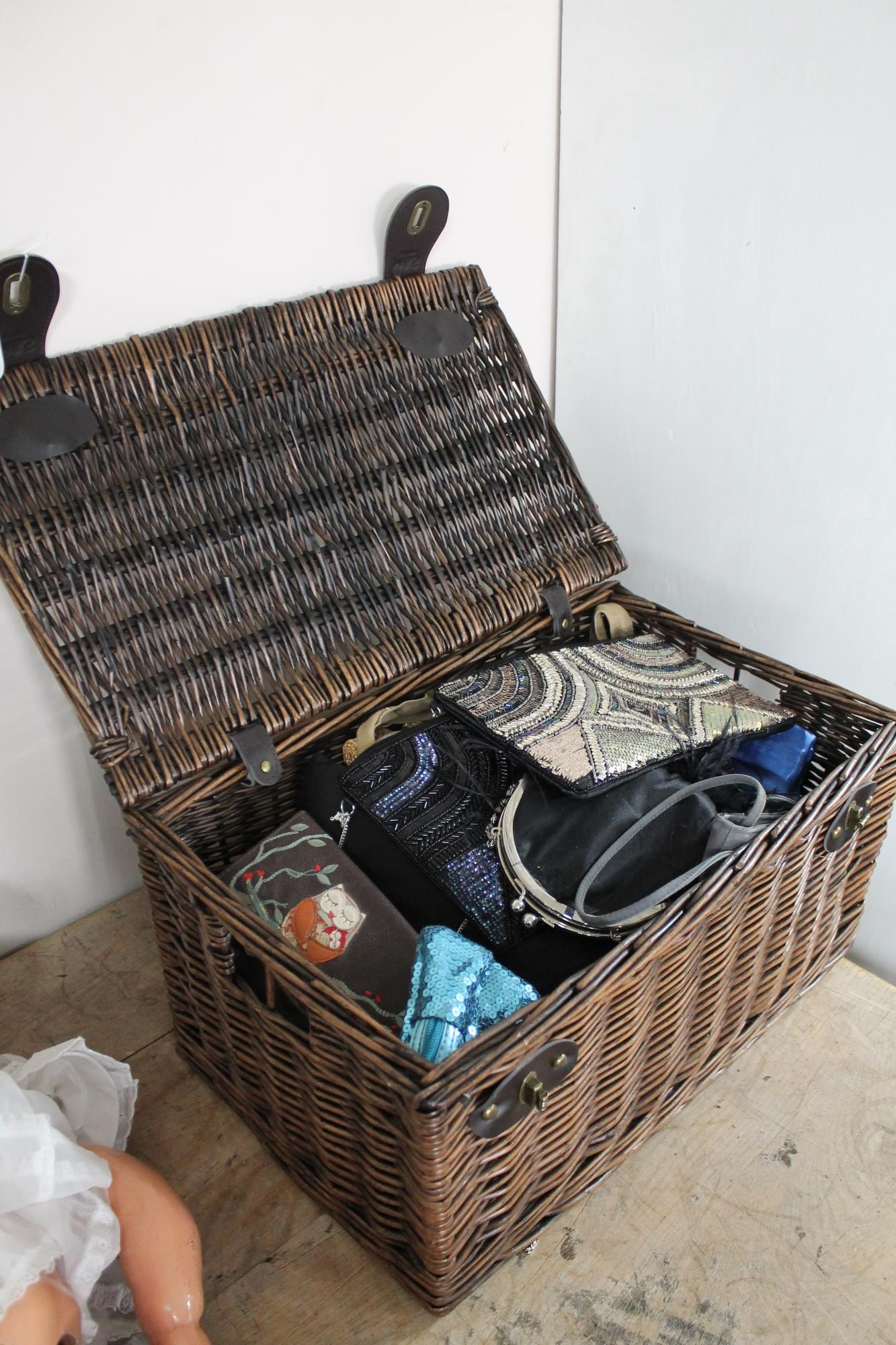 Lot 90 - A wicker basket containing a collection of lady's handbags