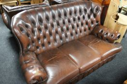 A three piece brown leather chesterfield style lounge suite