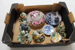 A box containing decorative china frog figures,
