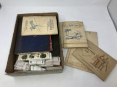 An early twentieth century album of world stamps together with an album of cigarette cards by