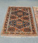 An Afghan Bokhara rug on rust ground,