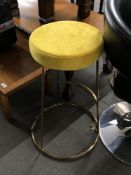 A pair of contemporary bar stools with mustard colour seats