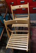 A set of four folding beech chairs