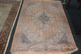 A fringed eastern rug on peach ground,