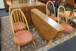 An Ercol elm flap sided table and four chairs