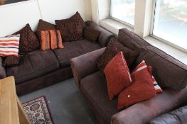 A brown suede three seater settee with scatter cushions together with the matching armchair