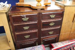 An Edwardian mahogany six drawer chest with cupboard base