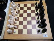 A beech chess board with carved resin pieces
