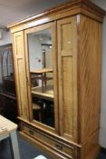 An Edwardian mirrored door wardrobe fitted with a drawer