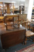 An early 20th century oak flap sided table and three chairs