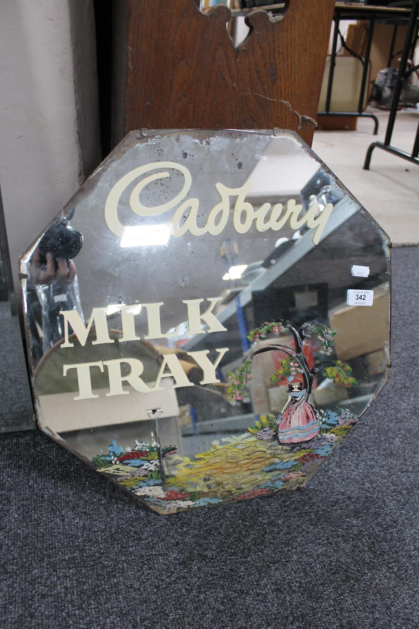A frameless mirror with milk tray advertising