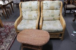 A pair of conservatory chairs and a small wicker low table