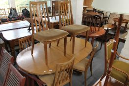 A teak extending dining table and six chairs