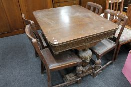 An early twentieth century carved oak table and four chairs