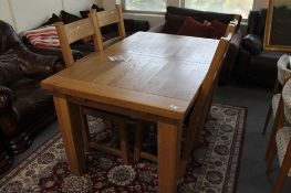 A light oak extending dining table and four ladder backed chairs