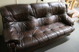 A three piece brown leather lounge suite with wooden frame
