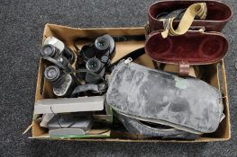 A box of binoculars, cameras,