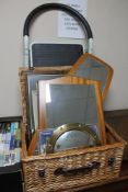 A wicker crate of teak framed mirrors, pictures and prints,