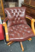 A Burgundy buttoned leather swivel chair