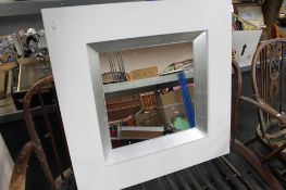 A white contemporary framed mirror CONDITION REPORT: This is 89cm by 89cm by 7.