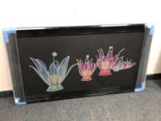 A floral picture in a black frame depicting flowers