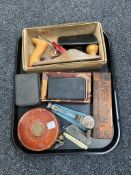 A tray of Chapman woodworking plane, vintage leather tape measure, pocket knives,