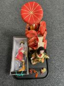 A tray of three figures of geisha on wooden stands