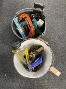 A plastic bucket and an enamel bucket containing assorted hand and power tools