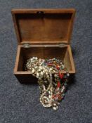 An antique inlaid wooden jewellery casket containing beads, necklaces,