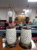 A pair of cream pottery table lamps on wooden bases