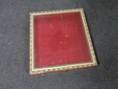 A gilt framed counter topped display cabinet with red velvet lining