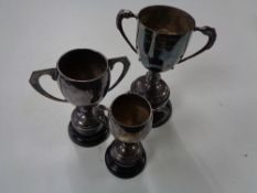 Three silver plated trophies on stands