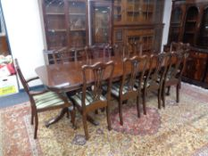 A Regency style twin pedestal extending dining table with two leaves and ten dining chairs