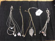 Approximately thirteen silver pendants