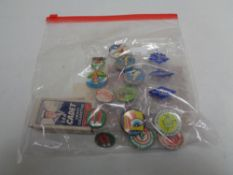A collection of vintage pin badges and sweet cigarette cards