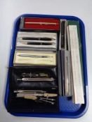A tray of cased drawing instruments, slide rule, pens, Papermate, Parker,