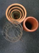 Two terracotta planters and a chimney pot together with three wrought metal stands