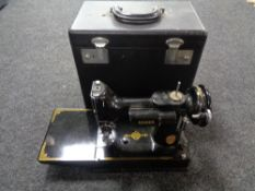 A small Singer hand sewing machine in carry case