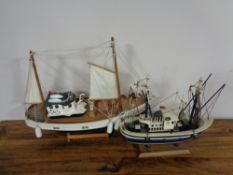 Two wooden model fishing trawlers on stand