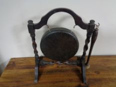 An antique gong and beater on oak stand