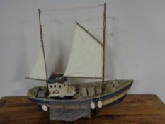 A wooden model of a fishing trawler on wooden stand