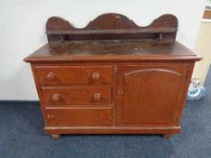 A Victorian pine sideboard fitted with cupboard and three drawers with shelf above