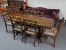 An oak refectory dining table together with six ladder backed chairs