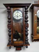 An early twentieth century mahogany eight day wall clock with brass and enamelled dial