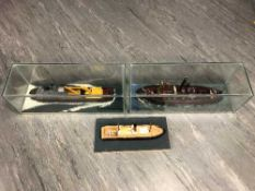 Three model ships, two under glass domes, longest 61cm.